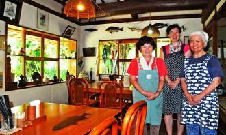 30周年を迎え、スタッフと一緒に「いつでもゆっくりしてって」と笑顔を見せる店主の奥田伶子さん(右)=竹富町西表島・唐変木