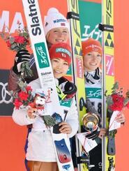 2位になり表彰式で笑顔を見せる高梨沙羅(手前)。上は優勝したマーレン・ルンビ、右は3位のカタリナ・アルトハウス=宮の森