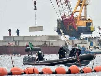 トンブロックを台船から作業船へ積み替えるクレーン=6日午前11時10分、沖縄県名護市辺野古沖