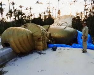 暴風によって倒れ、損壊した高さ約25メートルの「琉球金宮観音菩薩像」=30日、沖縄市知花・東南植物楽園