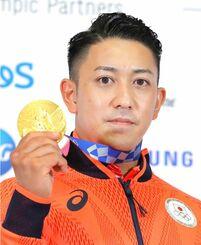 記者会見で空手男子形で獲得した金メダルを手にする喜友名諒=7日、東京都内(代表撮影)