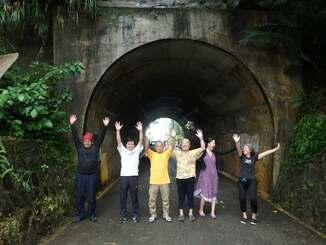 開通100周年を迎え、仲尾トンネルの前で万歳する仲尾区民=13日、名護市