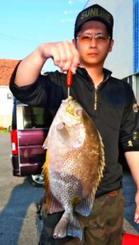山川漁港で42.5センチ、1.4キロのカーエーを釣った照屋将太さん=24日