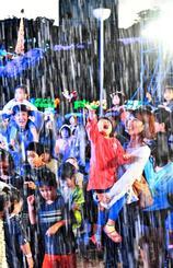 降り注ぐ人工雪に歓声を上げる子どもたち=22日午後6時、沖縄市・沖縄こどもの国(田嶋正雄撮影)