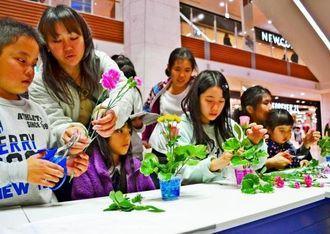 キクやカーネーションなどの花を切り分けてカップフラワーを作る参加者=23日、北中城村・イオンモール沖縄ライカム