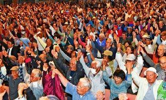 辺野古新基地建設阻止へ手をつなぎガンバロー三唱で気勢を上げる参加者=14日午後、宜野湾市・沖縄コンベンションセンター劇場棟