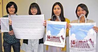 沖縄らしさを思い描いてデザインした紙袋と包装紙を手にする県立芸大の4人=沖縄タイムス社