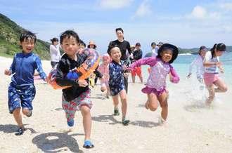 大自然の中で、知花くららさん(後方中央)と遊ぶ福島の子どもたち=5月30日、座間味村阿嘉・北浜ビーチ(知念豊撮影)