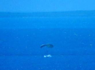 重い物資をパラシュートで下ろしたとみられ、着水の瞬間に水しぶきが上がった=20日、中城湾