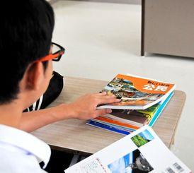 配布された東京書籍版の公民教科書を手にする中学生=竹富町内