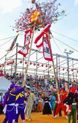 綱引き後に双方の健闘をたたえ合い、旗頭をぶつけ合う東と西=沖縄県与那原町・御殿山青少年広場