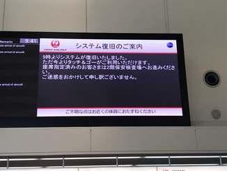 システムの復旧を知らせる日本航空の案内電子掲示板=8日午前9時41分、那覇空港