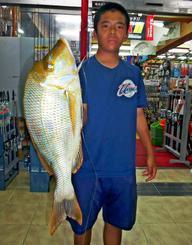 恩納村海岸で57.5センチ、2.28キロのタマンを釣った石原晃弥さん=5月18日