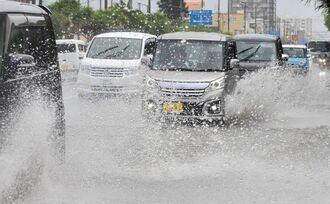 大雨で冠水した県道85号を水しぶきを上げて通行する車=26日午後1時58分、沖縄市海邦