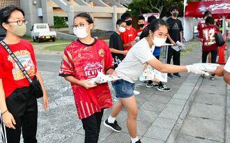 会場設営などのボランティアの後、FC琉球を応援するチラシを配る弘文館進学ゼミACTの中学生ら=17日午後、沖縄市・タピック県総ひやごんスタジアム