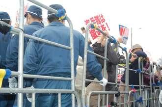 機動隊に排除され、ゲート横の柵に閉じ込められた座り込み市民ら=20日午前9時、名護市辺野古のキャンプ・シュワブ前