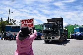 工事用ゲートから出ていく車両にプラカードを掲げて抗議する女性=7日午前11時すぎ、名護市辺野古の米軍キャンプ・シュワブゲート前