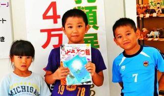 4万人目となった天願瑠人君(中央)と、弟の瑠偉君(右)妹の瑠彩ちゃん=19日、県立博物館・美術館