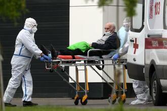 30日、新型コロナウイルスの感染疑いでモスクワの病院に搬送される男性(タス=共同)