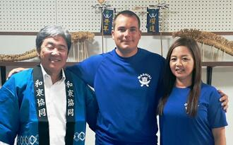 自治会の青いTシャツがお気に入りのコリンさん(中央)と妻の美奈子さん(右)、伊差川正美自治会長