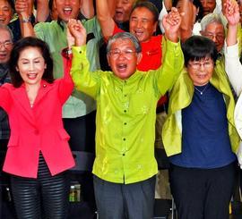 当確となり、支持者と喜ぶ赤嶺政賢氏(中央)=22日午後11時、那覇市おもろまちの選挙事務所