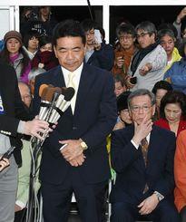 挙結果を受け、沈痛な表情で報道陣の取材に応える志村恵一郞氏と翁長雄志知事(右)