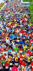 一斉にスタートするフルマラソンの参加者=17日午前9時すぎ、沖縄市・県総合運動公園前(古謝克公撮影)