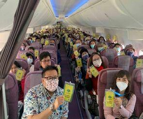 沖縄周遊フライトで、旅行保険加入を示す「カードホルダー」を掲げる乗客=1日、中華航空機内