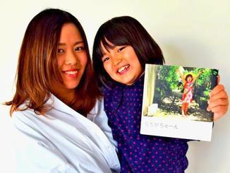 写真集を製作した國吉美和さん(左)と妹の来夏ちゃん=4日、県立芸術大学