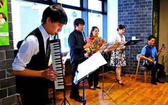 美しい音色を奏でる片山柊さん(左)ら新人演奏会出演者ら=31日午後、タイムスギャラリー