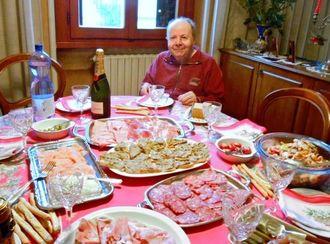 県出身家族が長年クリスマスをともに過ごすカルテエイ家のアトスさんと豪勢に並んだクリスマス料理=ミラノ市内