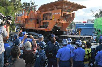 名護市の米軍キャンプ・シュワブゲート前を通るトレーラーに積まれた辺野古新基地建設の工事用大型機械=10月30日午前7時半すぎ