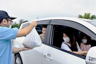 金武町商工会青年部のメンバー(左)からドライブスルーで弁当を受け取る町民ら=5日、同町