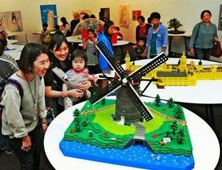 レゴブロックで作られた世界に魅了される人たち=9日午前、浦添市美術館