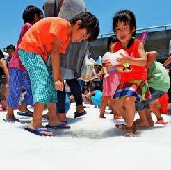 積もった雪で遊ぶ子どもたち=4日、豊見城市豊崎