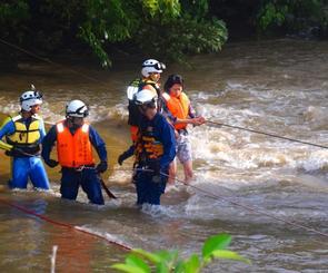 消防隊員の補助を受けながら救助される女性=5日午後7時2分、名護市・源河川