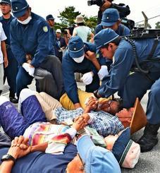 工事関係車両の進入を阻止しようと、座り込んで抗議する住民ら=12日午前9時32分、東村高江・北部訓練場メインゲート前(渡辺奈々撮影)