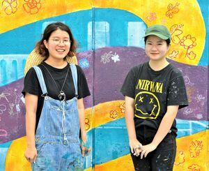 完成した壁画の前で笑顔を見せる制作者の(左から)大城可奈子さんと金城妃美佳さん。ライン上の花は子どもたちが描いた=6月20日、沖縄市・コザ運動公園