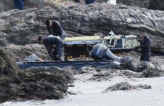 回収した機体の一部をゴムボートに乗せる米兵ら=17日午前11時15分ごろ、名護市安部の海岸