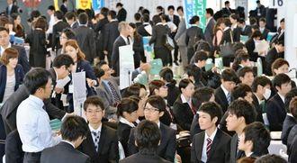 企業の人事担当者から業務内容などを熱心に聞く大学生=8日、宜野湾市・沖縄コンベンションセンター展示棟