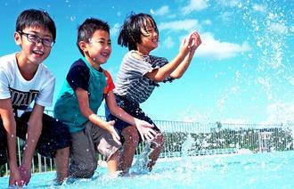 青空の下、道の駅「ぎのざ」の水遊び広場ではしゃぐ子どもたち=13日午後、宜野座村漢那(下地広也撮影)