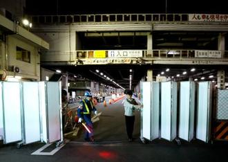 豊洲市場への引っ越し調整期間を終え、築地市場の正門を閉鎖する都職員=17日午後8時、東京都中央区