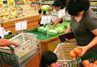 食料品を積んだ船が7日ぶりに久米島町に到着し、店に駆け付けた町民ら=18日、町謝名堂のAコープ久米島店(比嘉正明通信員撮影)