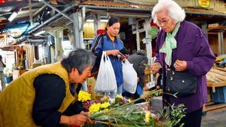 正月を迎える準備で花を買い求める客ら=30日、那覇市樋川の農連市場