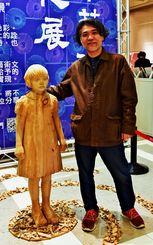 日本芸術文化展の会場入り口に展示された木彫「森の中の記憶」と儀保克幸さん=台北市内