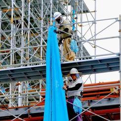 台風の接近に備えて工事現場のネットをロープで固定する作業員=20日午後、那覇市旭町