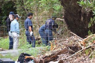 遺体遺棄現場の近くで金属探知機をつかう捜査員ら=2日午後0時30分ごろ、恩納村安富祖