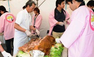 豚の丸焼きなどの試食が振る舞われた「まーさんシシの日」のイベント=4日、那覇市の沖縄セルラーパーク那覇