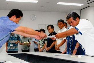 井上防衛局長(左)に抗議するうるま市議会基地対策委員会の喜屋武力委員長(右)=24日、沖縄防衛局