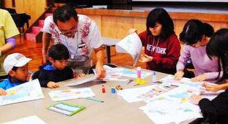 チラシを見ながら食材の産地を確認する子どもたち=18日、浦添市前田・JICA沖縄国際センター